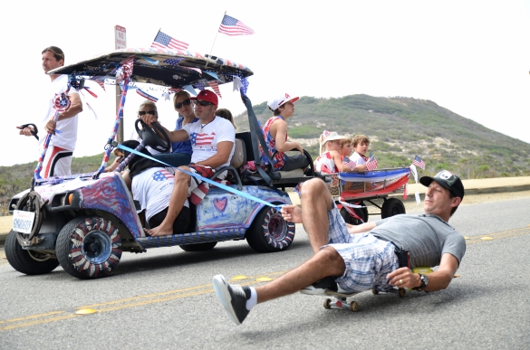 Drivers of a decorated golf cart string along a man on a skateboard during the Fourth of July Parade on Friday, July 4, 2014 at Point Dume in Malibu, Calif.